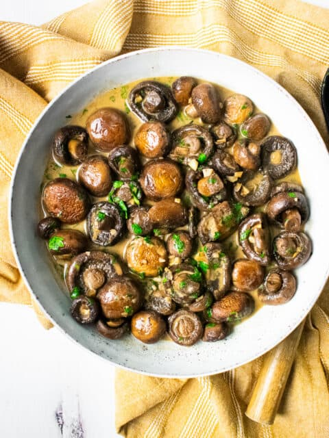 mushrooms in a bowl on a yellow napkin