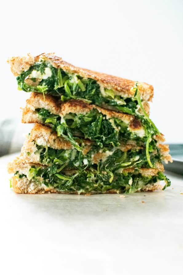 spinach filled grilled cheese stacked on a plate