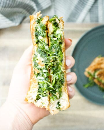 spinach filled grilled cheese being held